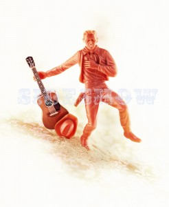 007 001 Red, orange plastic toy cowboy figurine with miniature acoustic guitar