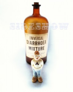 "009 001  Big brown glass bottle labeled "" Universal Diarrhoea Mixture"" behind a small boy figurine wearing a white sweater with an ""A"" on it."